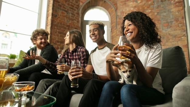 Dentro de casa. pessoas empolgadas assistindo jogo esportivo, campeonato em casa. grupo multiétnico de amigos, fãs torcendo pelo time de esporte favorito