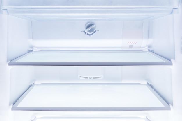 Dentro de geladeira limpa e vazia com prateleiras