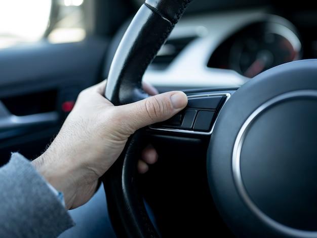 Dentro de um carro, a mão do homem segura o volante