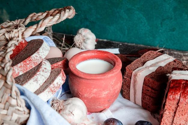 Dentro de uma cesta e fora embrulhado fatias de pão preto com pote de leite.