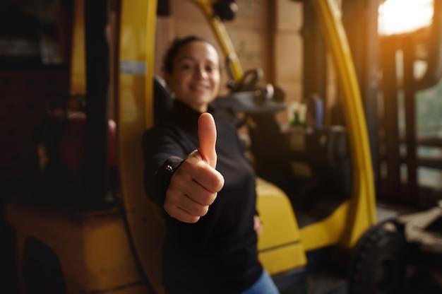 Dentro do armazém, a jovem está em frente a uma empilhadeira amarela e mostra o polegar para cima