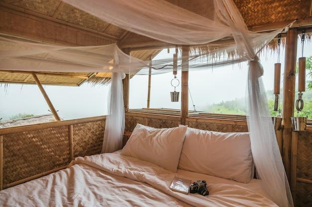Dentro do dormitório feito de palha de madeira com mosquiteiro, livro, câmera retro entre a serra no campo