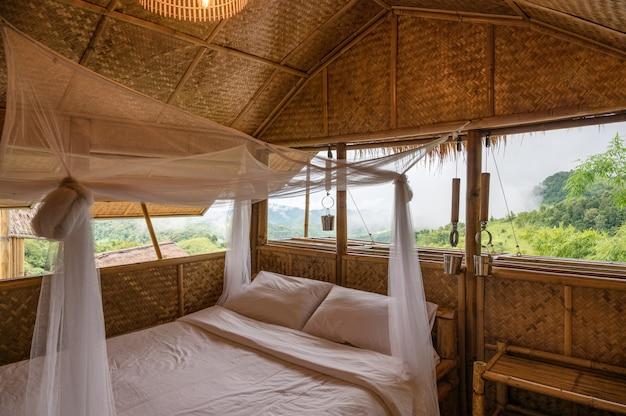 Dentro do quarto que é feito de palha de madeira com mosquiteiro entre a montanha no campo