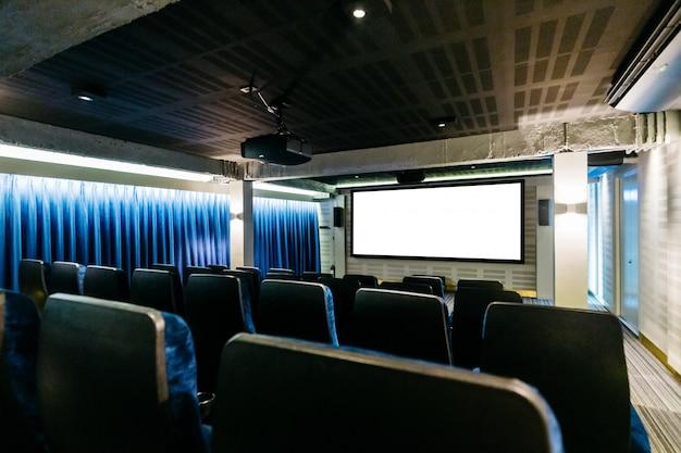 Dentro mini-teatro com assentos de cor azul, cortina azul e tela branca na frente.