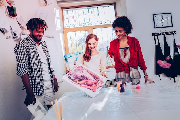 Departamento de arte. três alegres trabalhadores do departamento de arte sentindo-se satisfeitos com o resultado do trabalho