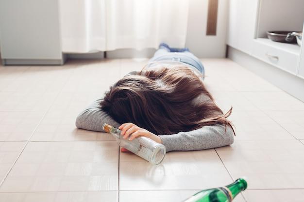 Dependência de álcool feminino. jovem mulher dormindo no chão da cozinha depois da festa segurando garrafa