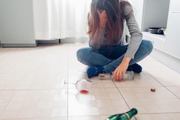 Dependência de álcool feminino. jovem mulher sentada no chão da cozinha depois da festa e segurando a garrafa. ressaca