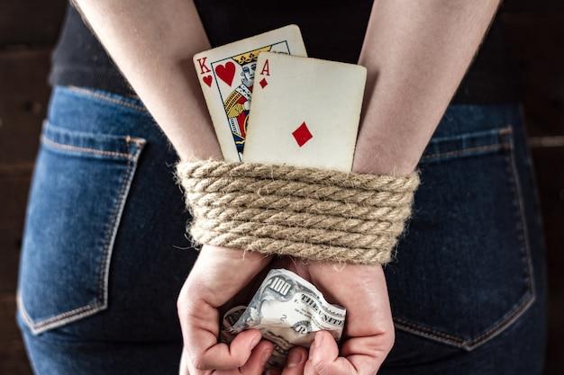 Dependência de cartão. dependência de pôquer, jogos de azar. uma jovem mulher com as mãos amarradas segurando cartas de jogar. conceito de jogo