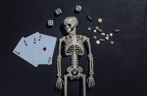Dependência de drogas e jogos de azar. esqueleto, quatro ases, dados, pílulas em fundo preto.