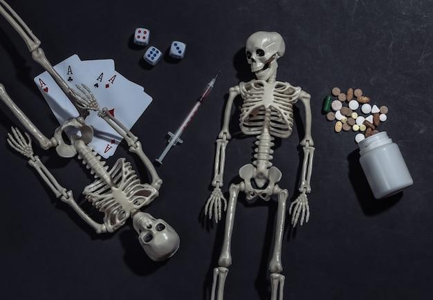 Dependência de drogas e jogos de azar. esqueletos, quatro ases, dados, pílulas e seringa em fundo preto.