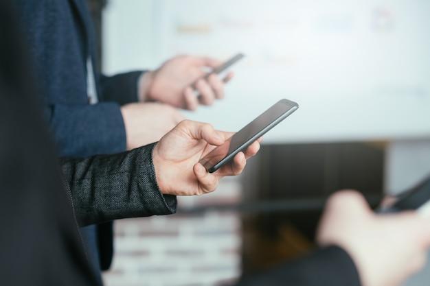 Dependência de mídia social. estilo de vida corporativo moderno. homens de negócios em fila, usando smartphones