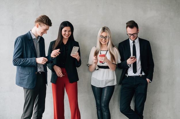 Dependência de mídia social. estilo de vida moderno. jovens colegas encostados na parede