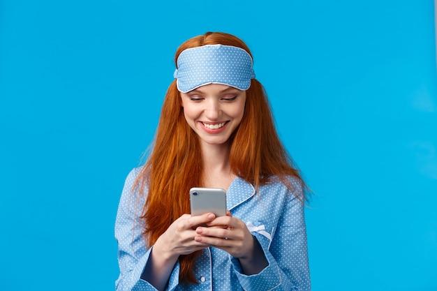 Dependência móvel, conceito de tecnologia e beleza. menina alegre, acordando e agarre o telefone, verificando mensagens, rolando feed de notícias no smartphone usando roupa de dormir, máscara de dormir, sorrindo