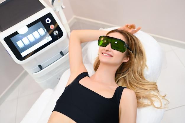 Depilação a laser e cosmetologia em salão de beleza. procedimento de remoção de pêlos. conceito de depilação a laser, cosmetologia, spa e remoção de pêlos. linda mulher loira, cabelo, remoção de axilas