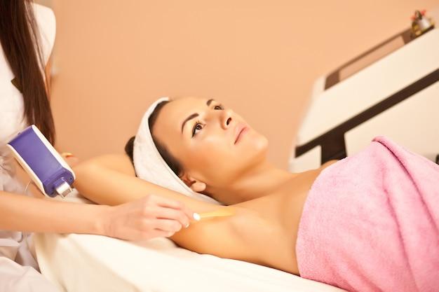 Depilação a laser na axila da mulher. mulher tendo tratamento de depilação a laser no salão.