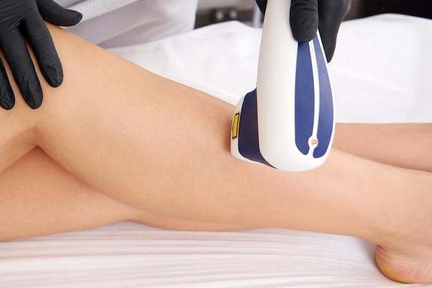 Depilação a laser nas pernas das senhoras no salão de beleza