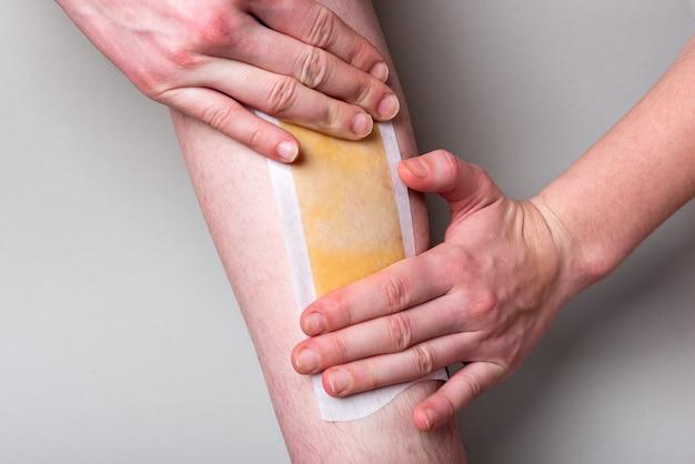 Depilação com cera nas pernas. removendo o cabelo das pernas na parede cinza.