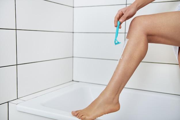 Depilação com conceito de creme de depilação. perna de mulher aplicando creme de barbear nas pernas e segurando uma lâmina de barbear no banheiro de casa