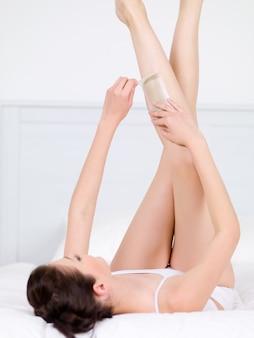 Depilação das pernas de uma jovem mulher bonita com cera - vertical