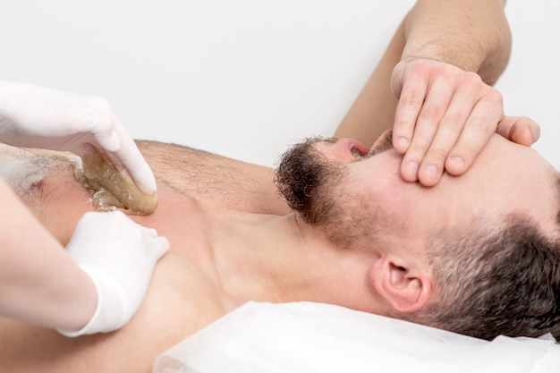 Depilação de peito de jovem com pasta de cera líquida pelas mãos de cosmetologista em salão de beleza