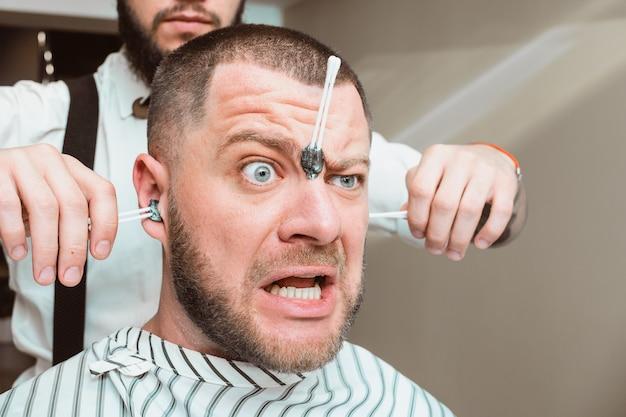 Depilação depilação nos ouvidos. puxando o cabelo das orelhas