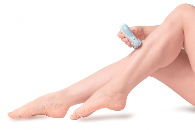 Depilação. mulher depilar as pernas com depilação com barbeador elétrico. isolado no fundo branco