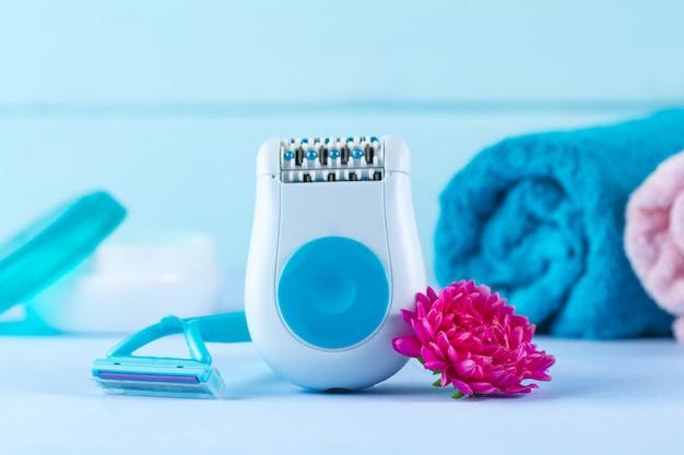 Depilador, creme, barbeador de mulher, toalhas e uma flor. depilatório. remoção de pêlos indesejados. conceito de depilação