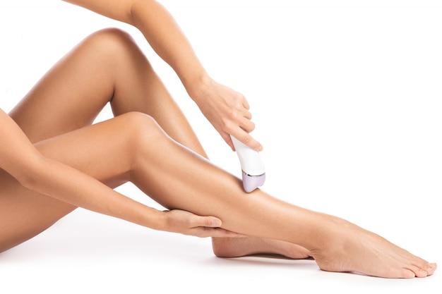 Depilador e pernas femininas