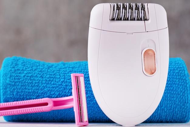Depilador, navalha de barbear e toalha de banho