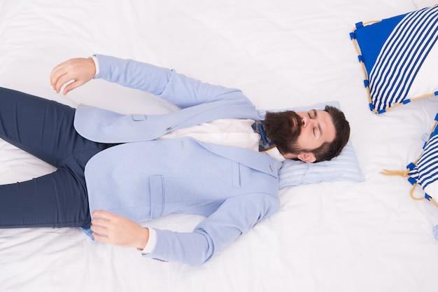 Depois da festa do noivo. groom dormir na cama. homem barbudo no desgaste do noivo. solteiro ou noivo. marido ou recém-casado. traje de casamento. loja de roupa masculina. trajes formais e de festa. moda e estilo para o noivo.