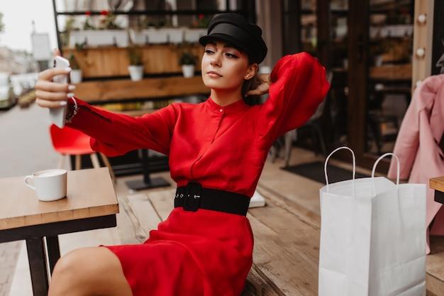 Depois das compras legais, jovem senhora com vestido de veludo vermelho e sacolas de compras, sentada do lado de fora do café e tirando uma selfie com seu novo iphone