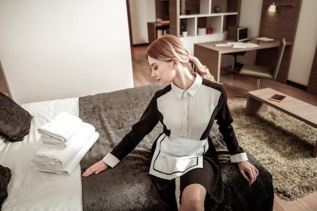 Depois de fazer a cama. empregada de hotel elegante se sentindo satisfeita depois de fazer a cama em um quarto espaçoso e bem iluminado