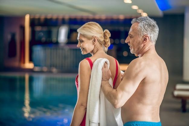 Depois de nadar. homem grisalho enxugando a esposa com uma toalha depois de nadar em uma piscina