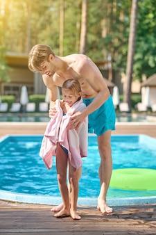 Depois de nadar. um jovem segurando seu filho com uma toalha segurando a piscina
