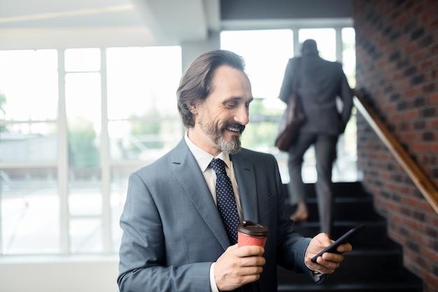Depois de receber o e-mail. homem de negócios maduro de cabelos grisalhos se sentindo satisfeito após receber o e-mail