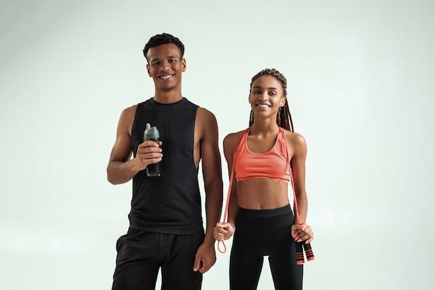 Depois de treinar um jovem casal africano esportivo e positivo em roupas esportivas, olhando para a câmera enquanto