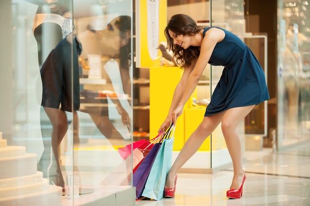 Depois de um dia de compras. comprimento total de uma jovem cansada de vestido azul tentando pegar as sacolas de compras pesadas