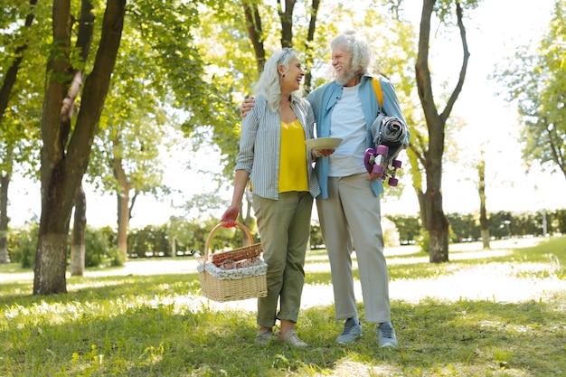Depois de um piquenique. casal simpático e positivo indo para casa depois de fazer um piquenique no parque