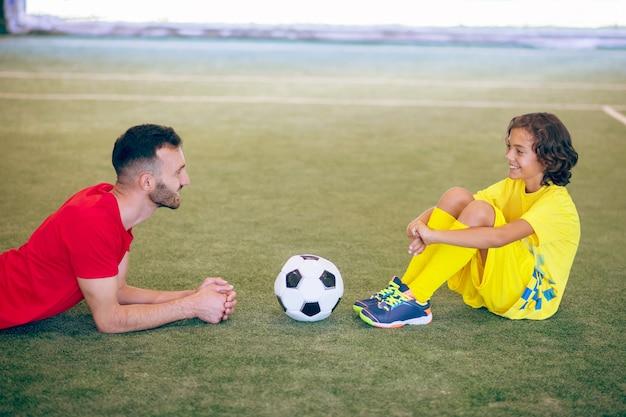 Depois do jogo. menino de uniforme amarelo descansando após o jogo e conversando com seu treinador