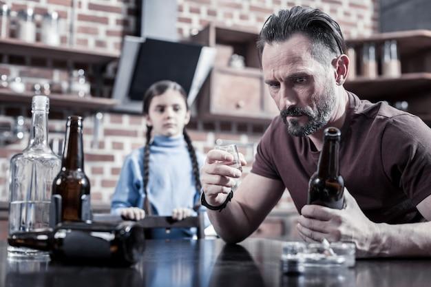 Depressão crônica. homem deprimido e desanimado segurando uma garrafa e olhando para ela enquanto bebe álcool em casa