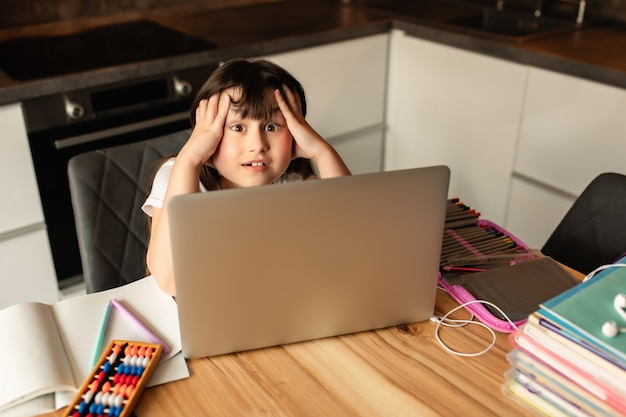Depressão e dor de cabeça do aprendizado on-line em casa. menina segura a cabeça durante uma aula on-line