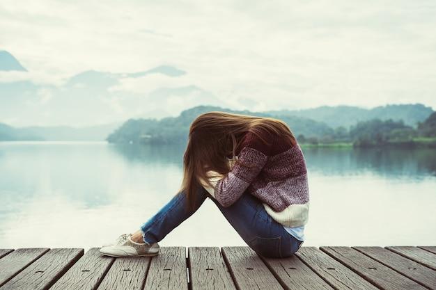 Deprimido e estressado mulher sentada no cais de madeira