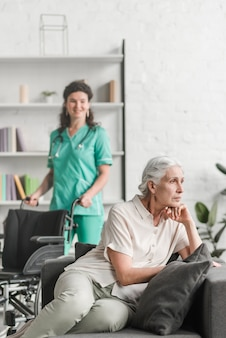 Deprimido, mulher jovem, sentar sofá, frente, enfermeira, ficar, com, cadeira roda