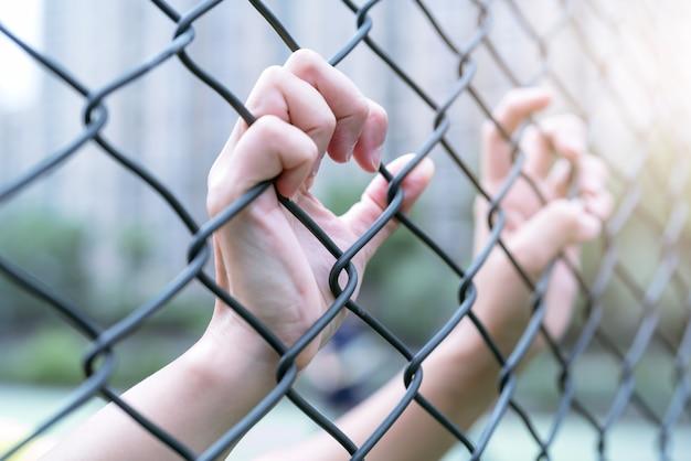 Deprimido, problemas e solução. as mulheres mão na cerca de arame.