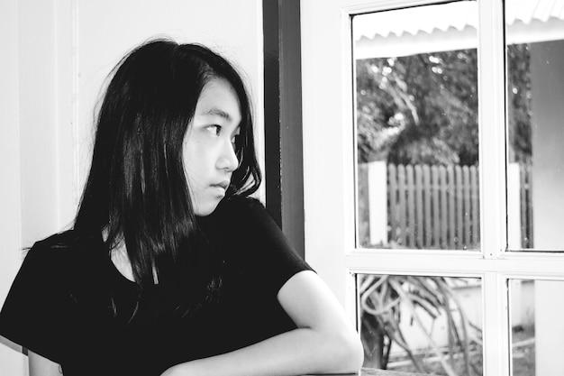 Deprimir e garota desesperada com ausente minded olhando do lado de fora