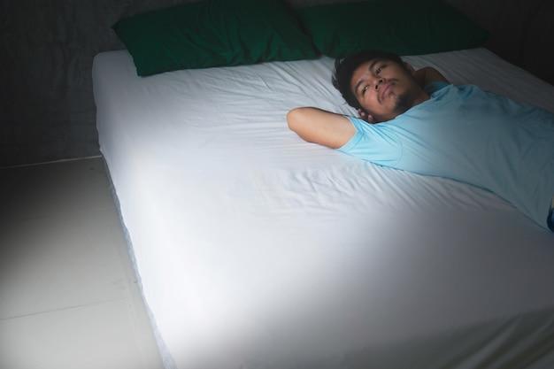 Deprimir e homem sem esperança, deitado na cama com o espírito ausente