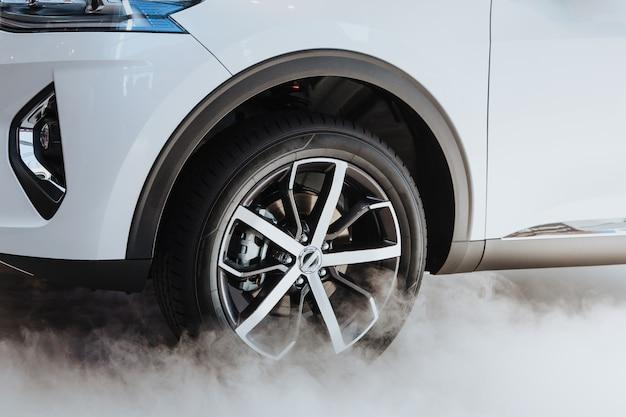 Deriva - o movimento do carro branco e roda preta com fumaça de pneu branco na estrada.