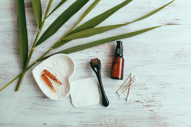 Dermaroller e soro ao lado de um creme de rosto anti envelhecimento indústria da beleza close-up dermaroller para terapia de micro agulhas médicas