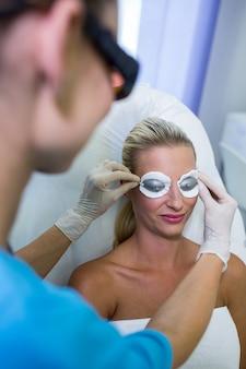 Dermatologista, ajustando um óculos de proteção