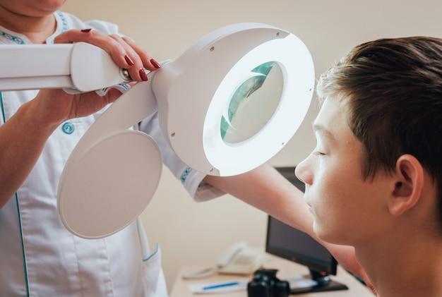 Dermatologista concentrado usando lupa médica na clínica
